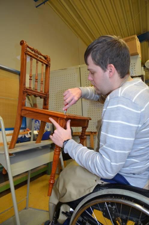 Mit geübter Hand entfernt Benedikt Fricke das kaputte Geflecht aus einem Stuhl.