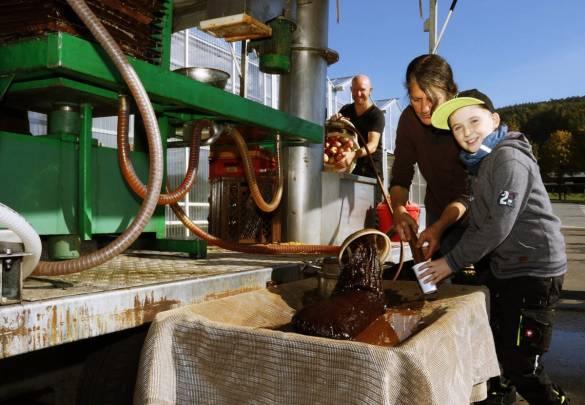 Peter Müller (von links) befüllt die Anlage mit Äpfeln. Anna Blume und Finn Smakulski (9 Jahre) nehmen denn gepressten Apfelsaft entgegen