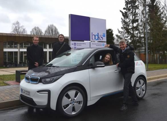 Manuel Krieg, Marlon Kapusta (beide Regionalmanagement Nordhessen), Karin Heyne und Joachim Bertelmann (beide bdks) freuen sich über den BMW i3, der jetzt den Mitarbeiter*innen der bdks für Dienstfahrten zur Verfügung steht